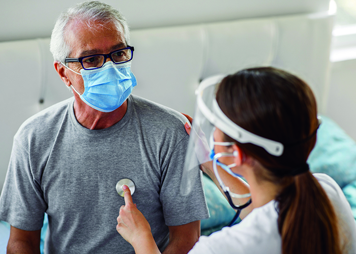 A masked male patient having his heart checked with a stethoscope by a masked female clinician.