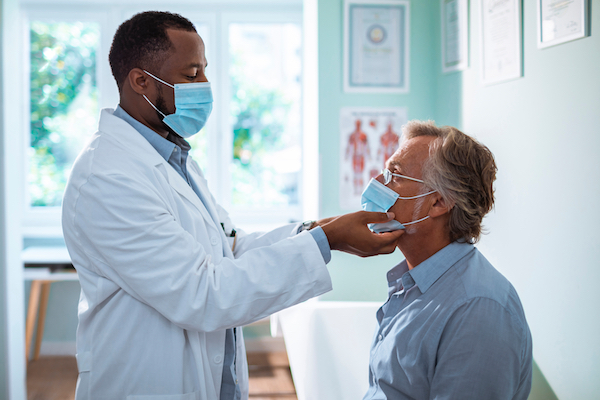 Doctor examining an adult male patient.