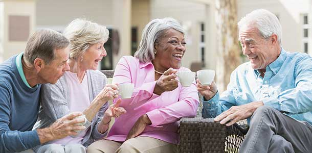 Senior friends outdoors drinking coffee.