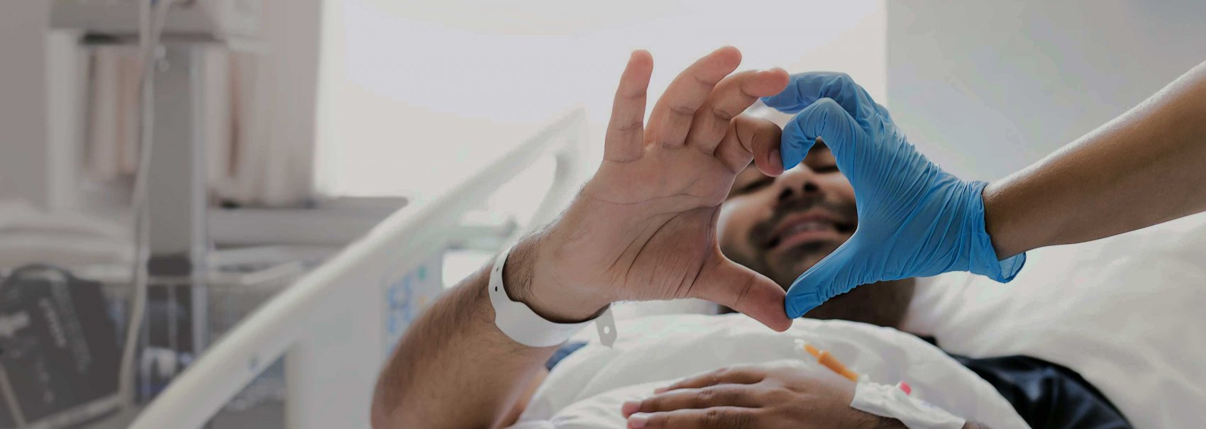 Healthcare worker and patient making a heart shape with hands